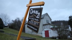 For Sale sign leaned over in foreground with country house behind it (HD) - stock footage