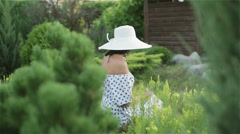 Middle aged woman in sun hat and dress among green trees and grass. Stock Footage