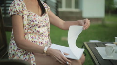 Pretty woman in nightie turns the page of the notebook and write a letter. Stock Footage