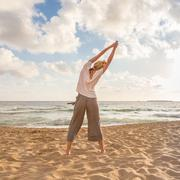 Woman practicing yoga on sea beach at sunset. Stock Photos