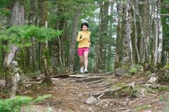 Young Japanese woman trail running at Mount Daibosatsu, Yamanashi Prefecture, - stock photo