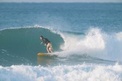 Japanese surfer riding wave - stock photo