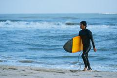 Japanese surfer walking on the beach - stock photo