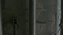 A close up pan shot of paint peeling off of a concrete wall to an open door in Stock Footage