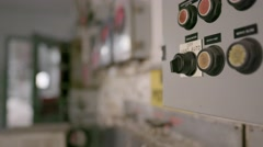Rack focus from a control panel to an open door in an abandoned factory. Stock Footage