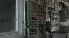 A pan shot of rusted control panels on a wall of an abandoned factory. Stock Footage