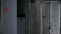 Pan shot of a wall of electrical cabinets in a run-down, abandoned factory. - stock footage