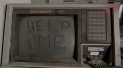 "A still shot of an old, dusty monitor with the words ""help me"" drawn on it in Stock Footage"