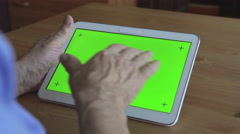 BACK VIEW: Aged male hands types on a white tablet PC (green screen) - stock footage