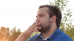Portrait of a lonely man smoking a cigarette in sunlight Stock Footage