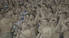 Fans with bare torsos clap at the stadium Stock Footage