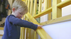 Cut child runs down some house steps Stock Footage