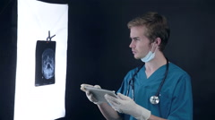 Male doctor at work in medical clinic examining x-ray plates of head Stock Footage