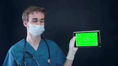 Male doctor holding, showing digital tablet with green screen Stock Footage