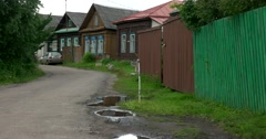 Quiet, empty village street after the rain, wooden houses Stock Footage