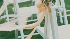 Wedding decor on the chairs , ribbons and flower on white chairs Stock Footage