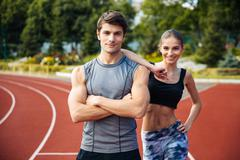 Young man and woman standing on athletics race track Stock Photos