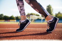 Close up portrait of a female runner feet running - stock photo