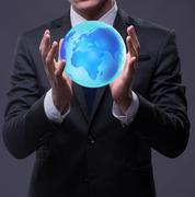Young businessman in globalisation concept holding earth Stock Photos
