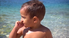 Cute boy stares at something at the sea Stock Footage