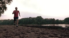 Male runner in red tshirt running along sandy riverside. Super slow motion Stock Footage