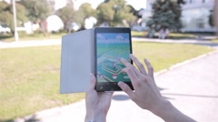 Pokemon Go app being played by a man on his tablet - stock footage