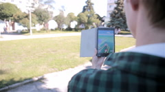 Young hipster man using tablet in the city park playing pokemon go Stock Footage