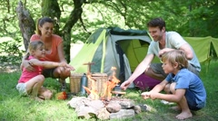 Family camping and cooking sausages in campfire Stock Footage