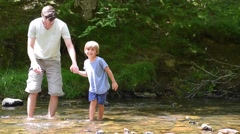 Daddy and son crossing river barefoot - stock footage
