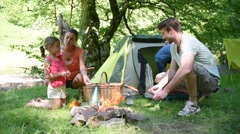 Family camping and cooking sausages in campfire - stock footage