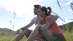 Couple sitting in country field on summer day - stock footage