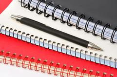 Spiral notepads and ball pen on white background - stock photo