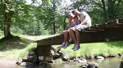 Family sitting on a bridge crossing mountain river - stock footage
