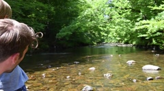 Father and son throwing pebbles in river water - stock footage