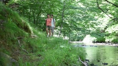 Couple rambling in forest path by river Stock Footage