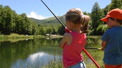 Kids fishing by mountain lake in summer - stock footage