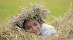 Young girl in a wreath resting in straw haystack Stock Footage
