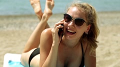 Woman lying on a sun lounger on the beach and talking on the phone. Stock Footage
