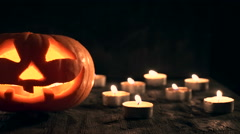 Carved Halloween pumpkin on a black background with lighted candles. Stock Footage