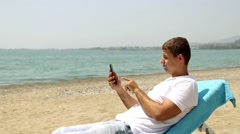 Man on the Internet with smartphone on the beach. - stock footage