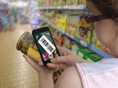Woman is shopping in supermarket and scanning barcode with smartphone in groc Stock Photos