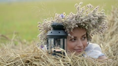 a young girl wearing a crown holding a lantern near the stacks of straw - stock footage