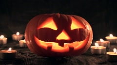 Carved Halloween pumpkin lights inside with flame on a black background Stock Footage