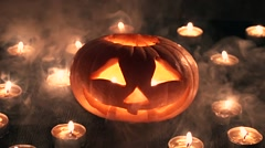Carved Halloween pumpkin lit a flame inside, around the smoke travel Stock Footage