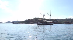 4k Indonesian sailing ship at sunny islands in Flores Sea Stock Footage
