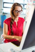 Female graphic designer working on computer at office Stock Photos