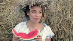 young girl in a wreath eats ripe watermelon near the stacks of straw - stock footage