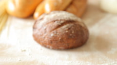 Freshly baked traditional bread cut in slices on a wooden table Stock Footage