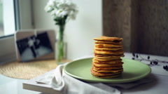 Man hand puts piece of butter on stack of pancakes. Pancake breakfast - stock footage