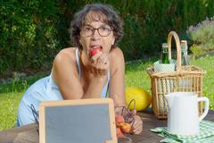 Beautiful mature woman eating a peach Stock Photos